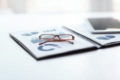 Περιοχή αποκομμάτων με την οικονομική έκθεση και γυαλιά σχετικά με τον υπολογιστή γραφείου στοκ εικόνες