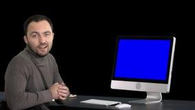 Περιστασιακός επιχειρηματίας που χαμογελά και που μιλά στη κάμερα που παρουσιάζει κάτι στο όργανο ελέγχου του υπολογιστή, άλφα κα απόθεμα βίντεο