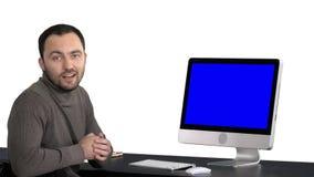 Περιστασιακός επιχειρηματίας που χαμογελά και που μιλά στη κάμερα που παρουσιάζει κάτι στο όργανο ελέγχου του υπολογιστή, άσπρο υ απόθεμα βίντεο