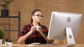 Περιστασιακός καφές κατανάλωσης γυναικών στο σύγχρονο δωμάτιο γραφείων μπροστά από τον υπολογιστή απόθεμα βίντεο