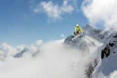Πετώντας σκιέρ στα χιονώδη βουνά Ακραίος χειμερινός αθλητισμός, αλπικό σκι στοκ εικόνα
