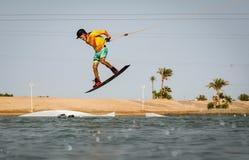 Πηδώντας κίνηση τεχνάσματος αέρα αθλητικών τύπων Wakeboarding στο cablepark, τον ενεργό αθλητισμό και τον τρόπο ζωής στοκ φωτογραφία
