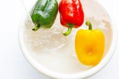 Πιπέρι κουδουνιών που ενυδατώνεται στο νερό Πλύσιμο των φρέσκων λαχανικών στο λευκό στοκ φωτογραφία με δικαίωμα ελεύθερης χρήσης