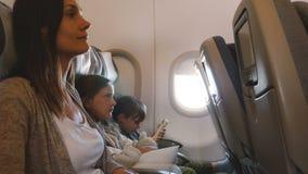 Πλάγια όψη της νέας όμορφης μητέρας με δύο μικρά τρυπημένα παιδιά κατά τη διάρκεια της μακροχρόνιας πτήσης αεροπλάνων που πηγαίνε απόθεμα βίντεο