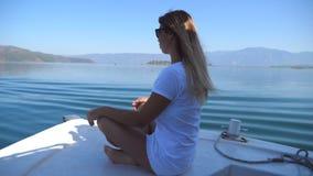 Πλάγια όψη της νέας συνεδρίασης γυναικών στο τόξο της βάρκας και του κοιτάγματος στο όμορφο τοπίο φύσης την ηλιόλουστη ημέρα ευτυ απόθεμα βίντεο