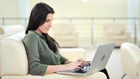 Πλάγια όψη που χαμογελά την όμορφη περιστασιακή επιχειρηματία που δακτυλογραφεί χρησιμοποιώντας το PC lap-top στο καθιστικό φιλμ μικρού μήκους