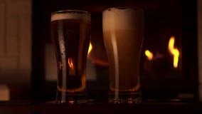 Πλήρης πυροβολισμός που χύνει τη φρέσκια μπύρα τεχνών στη διαφανή μεγάλη εστία γυαλιού στο υπόβαθρο απόθεμα βίντεο