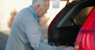 Πλήρωση του αυτοκινήτου με τις τσάντες αγορών απόθεμα βίντεο