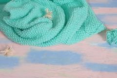 Πλεκτό τυρκουάζ πουλόβερ μαλλιού σε έναν πίνακα ρόδινος-μπλε με ένα μάλλινο νήμα και μικρά pom-poms στοκ φωτογραφία