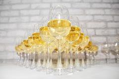 Πολλά goblets γυαλιού με το άσπρες κρασί και τη σαμπάνια στον πίνακα στοκ φωτογραφία