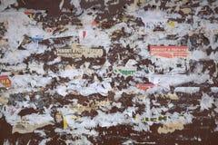 Πολλές σχισμένες αφίσες στον οξυδωμένο τοίχο χάλυβα στοκ φωτογραφία