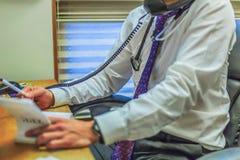 Πολλαπλό καθήκον γιατρών καθμένος στο γραφείο του στοκ εικόνες με δικαίωμα ελεύθερης χρήσης