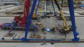 Πολλοί άνθρωποι που εργάζονται με τους γερανούς ατσάλινων σκελετών φόρτωσης και τους γερανούς φορτηγών στη βιομηχανική ζώνη, χρον απόθεμα βίντεο