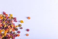 Πολύχρωμα ζυμαρικά με την προσθήκη της φυσικής φυτικής χρωστικής ουσίας Διεσπαρμένος σε έναν άσπρο πίνακα Τοπ άποψη, διάστημα αντ στοκ εικόνα με δικαίωμα ελεύθερης χρήσης