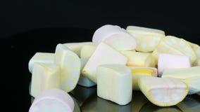 Πολύχρωμες μίνι marshmallow καραμέλες στην επιφάνεια καθρεφτών και ένα μαύρο υπόβαθρο Το πρόβλημα του διαβήτη και να παραφάει απόθεμα βίντεο