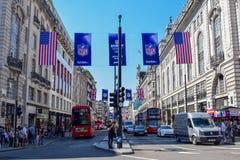 Πολυάσχολη οδός του Λονδίνου με τα εμβλήματα και τις σημαίες αμερικανικού ποδοσφαίρου στοκ εικόνα με δικαίωμα ελεύθερης χρήσης