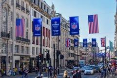 Πολυάσχολη οδός του Λονδίνου με τα εμβλήματα και τις σημαίες αμερικανικού ποδοσφαίρου στοκ εικόνα