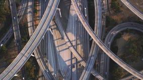Πολυάσχολος δρόμος οχημάτων εθνικών οδών πολλαπλάσιος με τις γέφυρες συνδέσεων τσιμέντου κυκλοφορίας στο εντυπωσιακό τοπ εναέριο  απόθεμα βίντεο