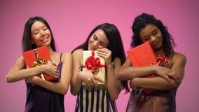 Πολυφυλετικές γυναίκες στις πυτζάμες που κρατούν τα κιβώτια δώρων, μυστικό κόμμα santa, εορτασμός απόθεμα βίντεο