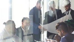 Πολυφυλετική ομάδα κατασκευαστών και αρχιτεκτόνων που συζητούν το σχεδιάγραμμα στο γραφείο φιλμ μικρού μήκους