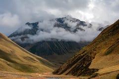 Πορεία βουνών στο φαράγγι που πηγαίνει μεταξύ των κλίσεων και των σύννεφων στοκ φωτογραφία με δικαίωμα ελεύθερης χρήσης