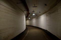 Πορεία μέσω μιας σκοτεινής κυρτής σχηματισμένης αψίδα σήραγγας με τους ελαφριούς τοίχους σε ένα παλαιό εγκαταλειμμένο κτήριο στοκ φωτογραφίες