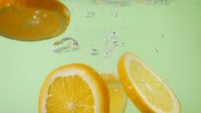 Πορτοκάλι που τεμαχίζεται φρέσκο πτώση στο νερό με τον παφλασμό φιλμ μικρού μήκους