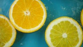 Πορτοκαλιά φρούτα με τους παφλασμούς νερού φιλμ μικρού μήκους