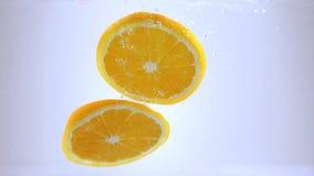 Πορτοκαλιά πτώση φετών στο νερό σε σε αργή κίνηση απόθεμα βίντεο