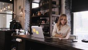 Πορτρέτο ενός ελκυστικού ξανθού κοριτσιού σε ένα άσπρο μεθοδικό πουκάμισο που ανοίγουν ένα lap-top και παίρνουν να εργαστούν Μια  φιλμ μικρού μήκους