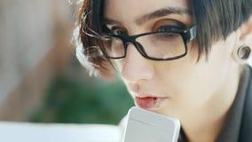 Πορτρέτο ενός ελκυστικού brunette με ένα διαπερασμένο χείλι Φορά τα γυαλιά, χρησιμοποιεί ένα τηλέφωνο Χέρια με το τηλέφωνο φιλμ μικρού μήκους