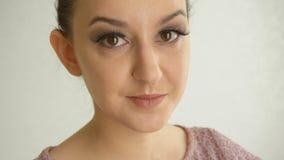 Πορτρέτο ενός κοριτσιού με τα μακροχρόνια ψεύτικα μαστίγια και τα καφετιά μάτια Χαριτωμένο θηλυκό πρότυπο με τη μόδα makeup στο ά φιλμ μικρού μήκους