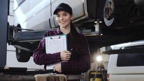 Πορτρέτο ενός κοριτσιού, ενός μηχανικού αυτοκινήτων σε ένα πουκάμισο καρό και μιας μαύρης ΚΑΠ, μπροστά από ένα αυτοκίνητο σε ένα  απόθεμα βίντεο