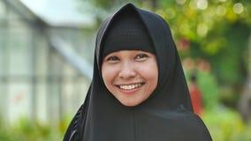 Πορτρέτο ενός νέου χαμογελώντας μουσουλμανικού κοριτσιού σε ένα μαύρο hijab απόθεμα βίντεο