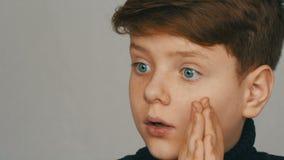 Πορτρέτο ενός ξανθού και μπλε-eyed αγοριού εφήβων αστείου που εκπλήσσει μπροστά από τη κάμερα στο άσπρο υπόβαθρο Συγκινήσεις φιλμ μικρού μήκους