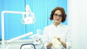 Πορτρέτο ενός όμορφου, νέου γιατρού γυναικών που φορά τα ιατρικά γάντια Γυναίκα οδοντικός βοηθός στα γυαλιά που βάζει στα γάντια φιλμ μικρού μήκους