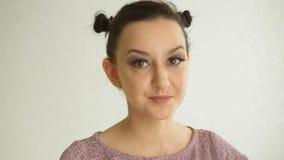 Πορτρέτο ενός χαμογελώντας κοριτσιού με τα μακροχρόνια ψεύτικα μαστίγια και τα καφετιά μάτια Καλό θηλυκό πρότυπο με το όμορφο mak απόθεμα βίντεο