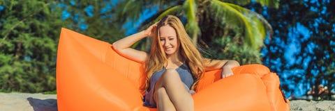 Πορτρέτο θερινού τρόπου ζωής της όμορφης συνεδρίασης κοριτσιών στον πορτοκαλή διογκώσιμο καναπέ στην παραλία του τροπικού νησιού  στοκ φωτογραφία με δικαίωμα ελεύθερης χρήσης
