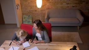 Πορτρέτο κινηματογραφήσεων σε πρώτο πλάνο της νέας καυκάσιας μητέρας που διδάσκει το μικρό όμορφο κορίτσι της και που δίνει της έ απόθεμα βίντεο