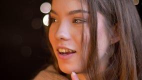 Πορτρέτο κινηματογραφήσεων σε πρώτο πλάνο της νέας καυκάσιας προσοχής κοριτσιών smilingly στη κάμερα και της σκέψης για κάτι στα  φιλμ μικρού μήκους