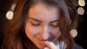 Πορτρέτο κινηματογραφήσεων σε πρώτο πλάνο της νέας καυκάσιας προσοχής κοριτσιών ταπεινά στη κάμερα στο θολωμένο υπόβαθρο φω'των φιλμ μικρού μήκους