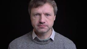 Πορτρέτο κινηματογραφήσεων σε πρώτο πλάνο του ενήλικου ελκυστικού καυκάσιου ατόμου που εξετάζει ευθέος τη κάμερα με τη σοβαρή έκφ απόθεμα βίντεο