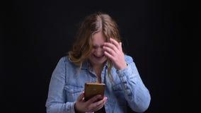 Πορτρέτο κινηματογραφήσεων σε πρώτο πλάνο του ενήλικου καυκάσιου ξανθού θηλυκού που αντιδρά στις κοινωνικές θέσεις μέσων που χρησ απόθεμα βίντεο