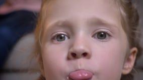 Πορτρέτο κινηματογραφήσεων σε πρώτο πλάνο του μικρού αρκετά καυκάσιου κοριτσιού με τις πλεξούδες που παρουσιάζουν γλώσσα της χαρω απόθεμα βίντεο
