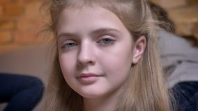 Πορτρέτο κινηματογραφήσεων σε πρώτο πλάνο του μικρού αρκετά καυκάσιου κοριτσιού που ρυθμίζει την τρίχα της και που προσέχει ήρεμα φιλμ μικρού μήκους
