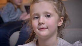 Πορτρέτο κινηματογραφήσεων σε πρώτο πλάνο του μικρού αρκετά καυκάσιου κοριτσιού με τις πλεξούδες που χαμογελά δειλά στη κάμερα στ απόθεμα βίντεο
