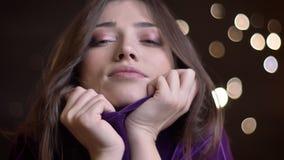 Πορτρέτο κινηματογραφήσεων σε πρώτο πλάνο του νέου αρκετά καυκάσιου θηλυκού που θερμαίνει το πρόσωπό της στο άνετο turtleneck που φιλμ μικρού μήκους