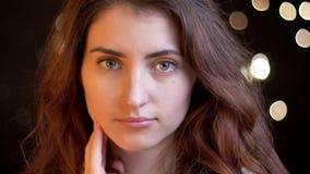 Πορτρέτο κινηματογραφήσεων σε πρώτο πλάνο του νέου καυκάσιου κοριτσιού με την κυματιστή προσοχή τρίχας σοβαρά στη κάμερα στο θολω απόθεμα βίντεο