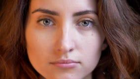 Πορτρέτο κινηματογραφήσεων σε πρώτο πλάνο του νέου καυκάσιου κοριτσιού με την κυματιστή προσοχή τρίχας ήρεμα στη κάμερα στο θολωμ απόθεμα βίντεο