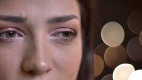 Πορτρέτο κινηματογραφήσεων σε πρώτο πλάνο του νέου όμορφου ευτυχούς θηλυκού που είναι στοχαστικό χαμόγελο και που εξετάζει τη κάμ φιλμ μικρού μήκους